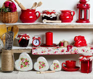 A rustic style. Ceramic tableware and kitchenware in red on the. Shelves Royalty Free Stock Photo
