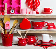 A rustic style. Ceramic tableware and kitchenware in red on the. Shelves royalty free stock images