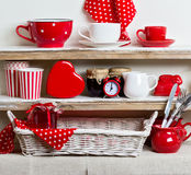 A rustic style. Ceramic tableware and kitchenware in red on the. Shelves Stock Photos