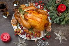 Rustic Style Christmas Turkey. Rustic style roasted Christmas turkey garnished with roasted garlic, lemon, and rosehips. Surrounded with rustic Christmas Stock Photo