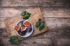 Rustic style Cut figs in flat dish on choppingboard Stock Image