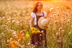Rustic style. Girl with sunflowers in the field stock photos