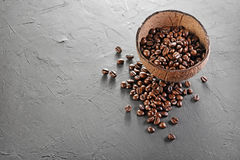 Rustic style image of coffee beans in coconut shell bowl. On dark textured background Royalty Free Stock Images