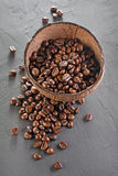 Rustic style image of coffee beans in coconut shell bowl. On dark textured background Stock Images