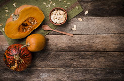 Rustic style pumpkins with seeds on green napkin and wood Royalty Free Stock Image