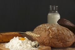 Rustic style still life with bread, egg, milk and a hill of wheat flour.  Stock Images