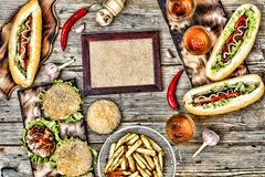 Hot dogs and beer on a wooden table. Rustic style, top view homemade burgers with beef. Rustic style, top view homemade burgers with beef, hot dogs and beer on a royalty free stock image