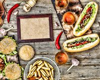 Hot dogs and beer on a wooden table. Rustic style, top view homemade burgers with beef. Rustic style, top view homemade burgers with beef, hot dogs and beer on a royalty free stock photo