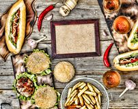 Hot dogs and beer on a wooden table. Rustic style, top view homemade burgers with beef. Rustic style, top view homemade burgers with beef, hot dogs and beer on a stock photography