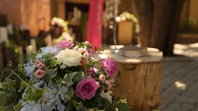Rustic style wedding ceremony decor with beautiful flower composition of pink and white roses. Rings lie on the stump stock video footage