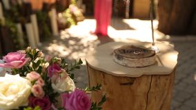 Rustic style wedding ceremony decor with beautiful flower composition of pink and white roses. Rings lie on the stump stock video