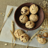 A rustic styled photo with grain homemade biscuits on a wooden plate, peanuts and ears Stock Images
