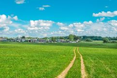 Rustic summer landscape. Village wooden houses, dirt road in green field in summer. Stock Photos