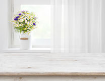 Rustic table in front of wild flowers on wooden window.  Stock Image