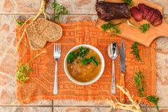 Rustic table lunch with bean soup and dried meat. royalty free stock image