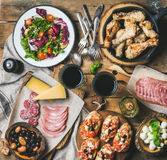 Rustic table set with salad, chicken, brushettas, snacks, red wine Stock Photos