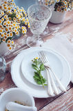 Rustic table setting. Chamomile flowers, white plates, wineglasses, vintage cutlery on a wooden background, home decor rustic table setting royalty free stock photography