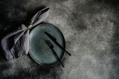 Rustic table setting. With grey ceramic plates and black metal cutlery on stone grey textured background with copy space stock photos