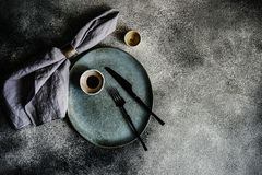 Rustic table setting. With grey ceramic plates and black metal cutlery on stone grey textured background with copy space royalty free stock image