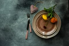 Rustic table setting. With ranunculus flowers on concrete background with copy space royalty free stock image