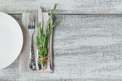 Rustic table setting with rosemary. On light wooden table with copyspace. Holidays decoration on Provence style. Romantic dinner. Top view with free space royalty free stock images