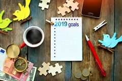 Rustic table with spiral notebook with `2019 goals`, cup of hot coffee, smartphone, money, compass, pen and other objects for deco royalty free stock image