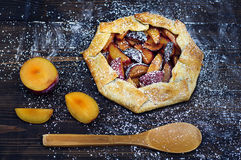 Rustic tart with plums and powdered sugar on the wooden table Stock Photo