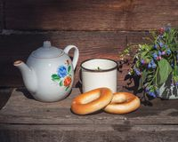 Rustic tea party in the open air, tea with bagels. A small bouquet of wildflowers stock photos