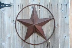 Rustic texas star. Rusting texas star on rotting wooden gate Stock Photos