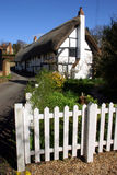 Rustic Thatched Cottage. A rustic thatched cottage complete with white picket fence. Very English Stock Photo