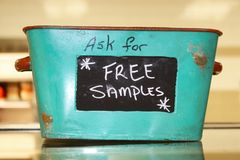 Rustic tin basket sitting on counter that says Ask for free samples stock photos