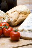 Rustic tomato lunch. A delicious spread of vine tomatoes, french bread and cheese on wooden table royalty free stock photography