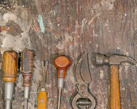 Rustic Tools. Vintage tools rest on an old paint stained workbench royalty free stock photos