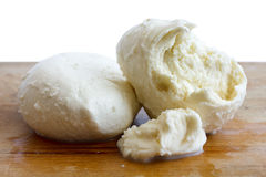 Rustic torn ball of mozzarella cheese on wood surface Stock Photos