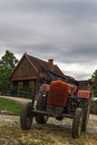 Rustic tractor and house Stock Photography