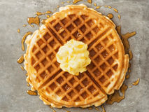 Rustic traditional waffle with butter and maple syrup. Close up of rustic traditional waffle with butter and maple syrup royalty free stock image