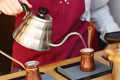 Rustic Turkish cezve, coffeepot, ibrik with boiled coffee beans, water, spices, cinnamon, salt on electric stove and wooden table. Selective focus Closeup Top royalty free stock photo