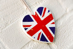 Rustic Union Jack heart decoration. Rustic wooden Union Jack heart decoration hanging on a painted white wall Royalty Free Stock Photo