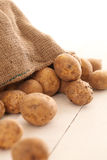Rustic unpeeled potatoes on a table Royalty Free Stock Photos