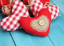 Rustic Valentine. Shabby chic red and white gingham hearts with rustic decorations of buttons, straw and hessian, valentine and Christmas decorations Royalty Free Stock Photography