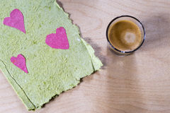 Rustic Valentines card with a cup of coffee. Rustic Valentines card with pink paper hearts on a green textures torn edged card with a cup of coffee on a wooden Royalty Free Stock Image