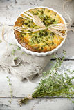 Rustic vegetables french quiche with peas on baking dish on vintage background with thyme bouquet Stock Photos
