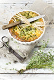 Rustic vegetables french quiche with peas on baking dish on vintage background with thyme bouquet Stock Photo