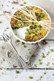 Rustic vegetables french quiche with peas on baking dish on vintage background Stock Photos