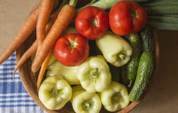 Rustic Vegetables. Rustic fresh vegetables, tomatoes, carrots, cucumbers and yellow peppers Royalty Free Stock Image