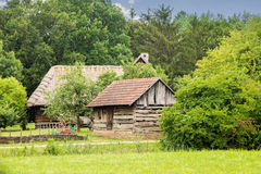 Rustic vintage peaceful country scene. Old wooden houses with historical agriculture tools royalty free stock image