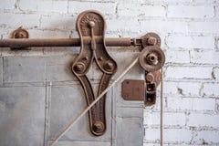 Rustic vintage pulley on metal industrial door Royalty Free Stock Images