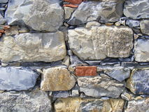 Rustic wall. Background of a wet old rustic wall made of many piled stones Royalty Free Stock Photo