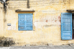 Rustic wall with blue door and window. Stock Photos