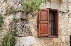 Rustic Wall and Window. A rustic window with wooden shutter on the outside of a Lebanese house Stock Photo